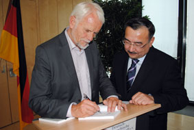 Wolfgang Börnsen signiert ein Exemplar seines Buches für Botschafter Dr. Nurlan Onzhanov.