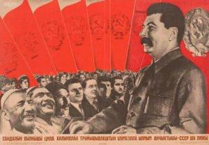 """Ein Plakat von Gustav Klutsis aus dem Jahr 1935: """"Es lebe die UdSSR – das Vorbild der Bruderschaft aller arbeitenden Völkerschaften der Welt!"""" Von der Bruderschaft, die in diesem aus der Sprache Mari übersetzten Plakat porträtiert wird, war in soziolinguistischer Hinsicht nicht viel zu sehen – Sprechverbote der Nationalsprache, Diskriminierungen und Repressionen von Völkerschaften kamen in der Sowjetunion nicht nur einmal vor."""